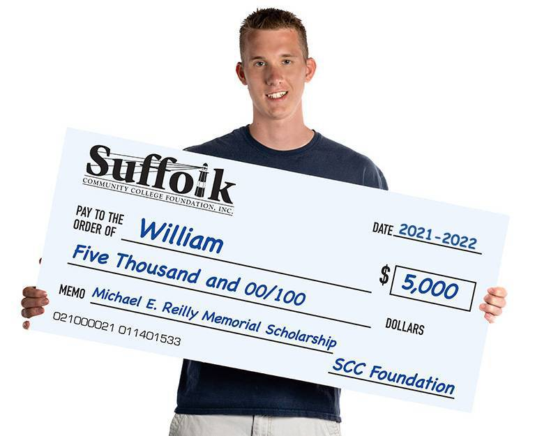 Man holding a giant check for scholarship fund
