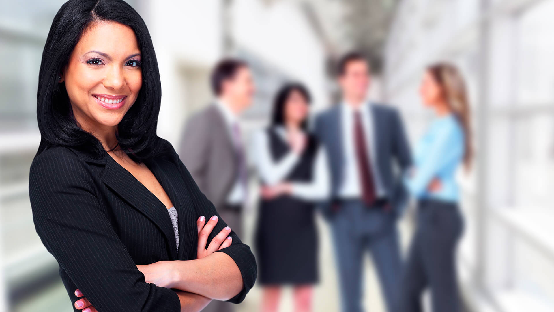 Business woman standing with folded arms.