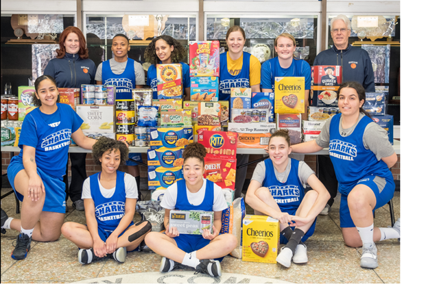 Suffolk Women's Basketball team poses with donated food
